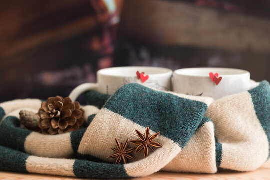 Romantic Love Nature Mood Creative Composition. Close-up Warm Green Beige Scarf Tied Two Mugs with Red Hearts. Spicy Drink. Background is firewood in fireplace. Stay warm together.