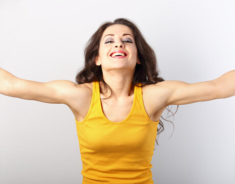Beautiful happy smiling brunette woman in yellow t-shirt gesturing the hug sign by arms on blue background. Closeup