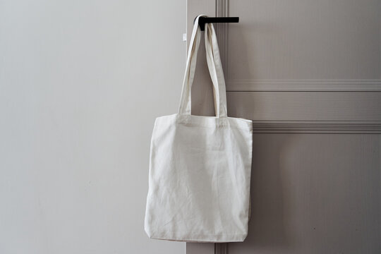 Eco friendly concept with white canvas tote bag hanging on door knob with two toned colored, Eco blank shopping sack with free copy space, Reduce plastic bags to reduce global warming. Canvas tote bag