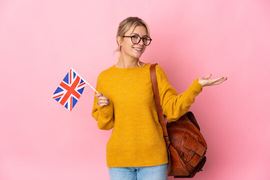 Young Russian woman holding an United Kingdom flag isolated on pink background extending hands to the side for inviting to come