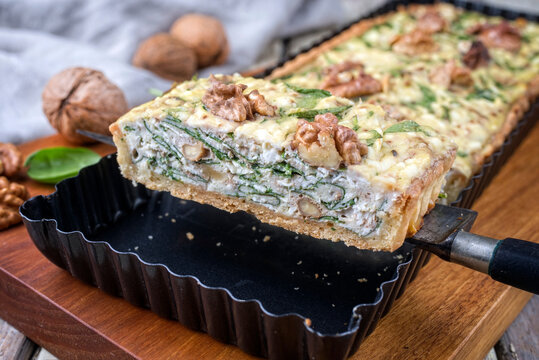 Traditional French Autumn walnut spinach tarte served as close-up in a backing form on an modern design wooden board