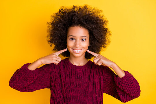 Photo of beautiful wavy hairdo dark skin schoolgirl indicate fingers toothy smile isolated on yellow color background