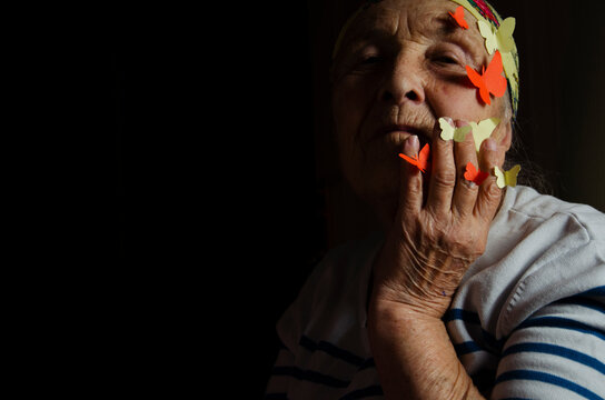 Wrinkled face with butterflies in the dark. An old woman with an ageless soul. Inner beauty. The tenderness of a woman. Maternal wrinkles. Caring and mercy. Fulfill desire. Freedom. To fly