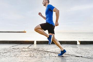 Wall Mural - man runner running in morning light of dawn along sea embankment