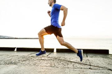 Wall Mural - male runner run in morning light of dawn along sea embankment