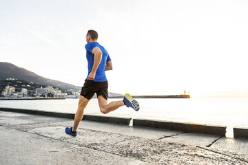 Wall Mural - man runner run in morning along sea embankment in city