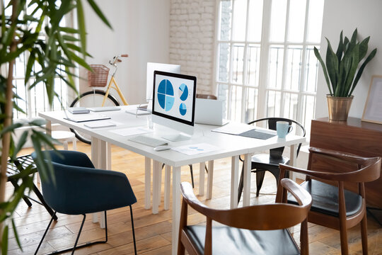 Modern loft office for small marketing team. Empty work space with white shared table, graphs for financial reports on computer monitors. Business interior, commercial real estate concept