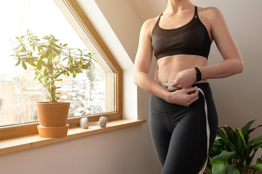 Young beautiful woman measuring waist with tape by a window in attic at sunny day. Healthy living and workout at home.