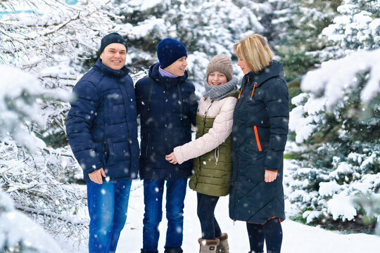 family portrait in the winter forest, parent and children, beautiful nature with bright snowy fir trees