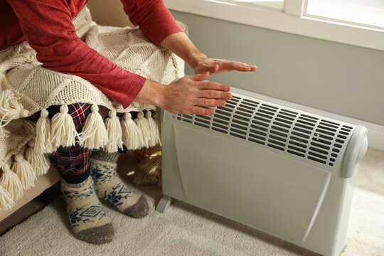Man warming hands near electric heater at home, closeup