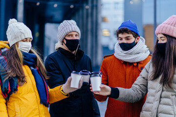 Group of four young people in facial protective masks meeting outdoor in winter day. New normal...
