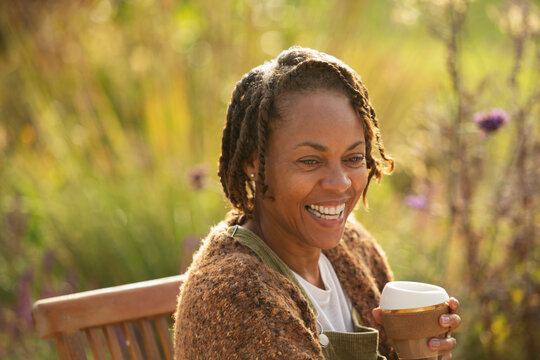 Happy woman with coffee laughing on sunny garden patio