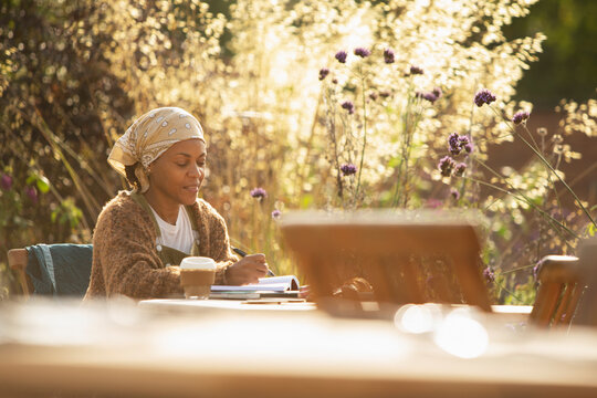 Woman working at cafe table in sunny garden