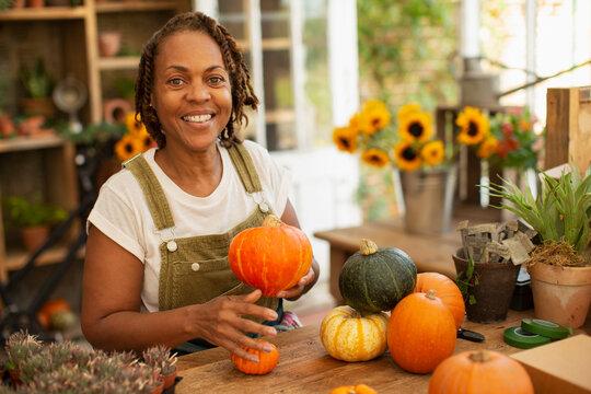 Portrait happy female florist arranging autumn pumpkins in shop