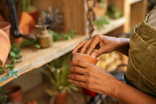 Close up woman with small flowerpot in plant nursery