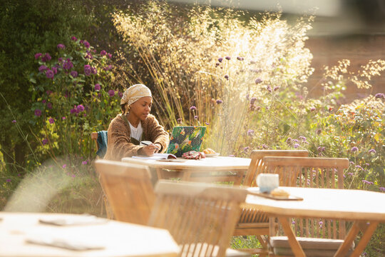 Woman working at laptop on sunny garden cafe patio