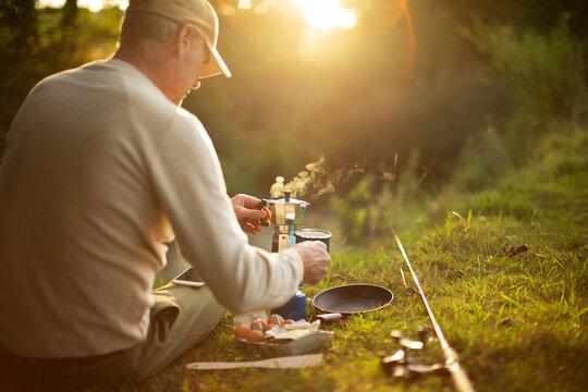 Man taking break from fly fishing pole making coffee on riverbank
