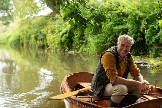 Portrait happy man fly fishing in boat on river