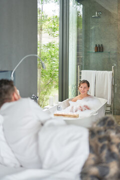 Couple taking bath and laying in bed in luxury modern hotel room