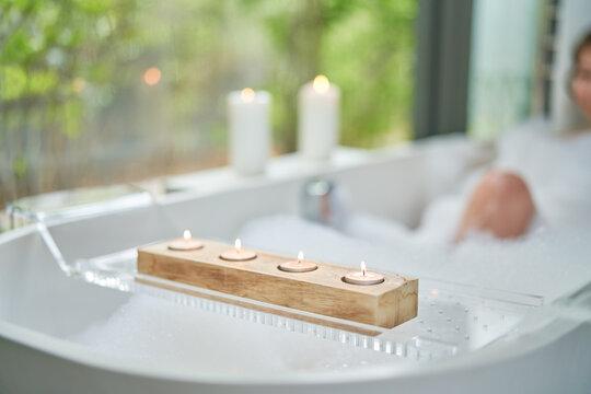 Tea light candles on tray over bubble bath