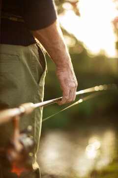 Close up man holding fly fishing pole