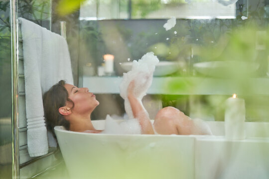 Playful woman in bubble bath in luxury soaking tub in bathroom