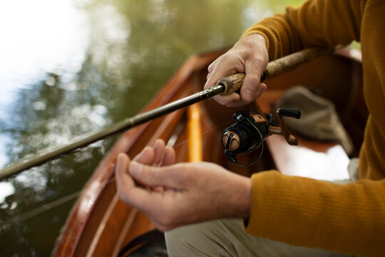 Close up man adjusting fly fishing line in boat