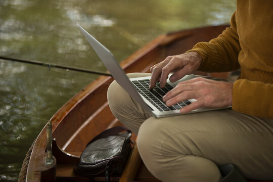 Man with laptop fly fishing in boat
