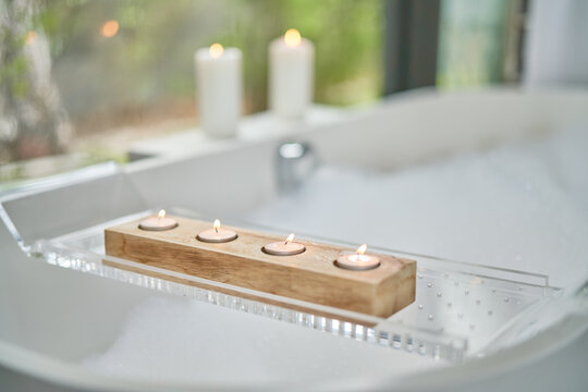 Tea light candles on tray over bubble bath