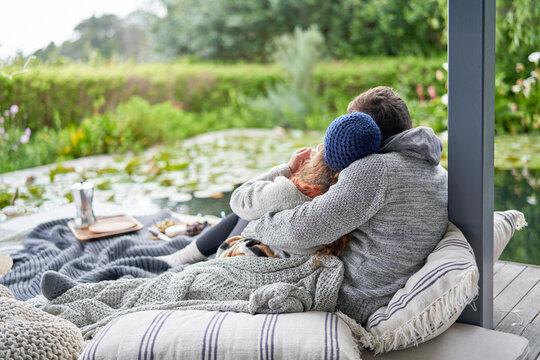 Affectionate couple cuddling on luxury patio