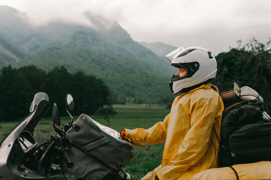 A girl in a yellow raincoat, shoe covers and a white helmet. Motorcyclism and travel. Sightseeing tour. Top of the Mountains. A gray day with thunderclouds. Difficult test and biker's outfit.