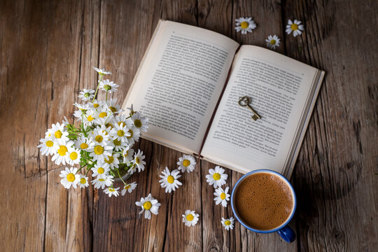 A cup of coffee with a book and daisies
