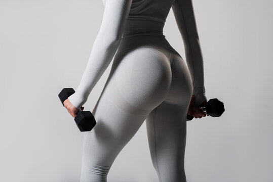 Sporty woman does the exercises with dumbbells on white background. Photo of muscular woman in sportswear on white background. Strength and motivation.