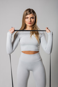 Health care concept. Beautiful woman with healthy skin, pony tail, has exercises with elastic band, dressed in sportsclothes, poses against white background