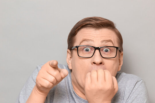 Portrait of shocked frightened man biting nails, pointing at something