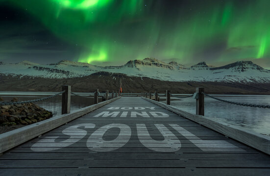 Body mind soul text on wooden pier outdoors in beautiful landscape scenery. Aurora borealis on the sky.