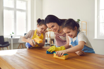 Loving twin sisters help their caring mother wash the kitchen table and clean the house. Family in...
