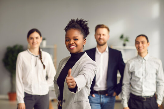 Smiling young woman giving thumbs-up together with diverse multiracial people in background. Good business idea, excellent choice, positive outcome, winning solution, success, job satisfaction concept