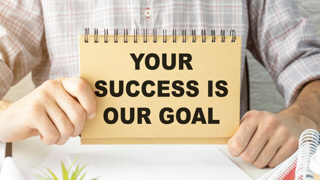Your success is our goal text on notebook in hands.