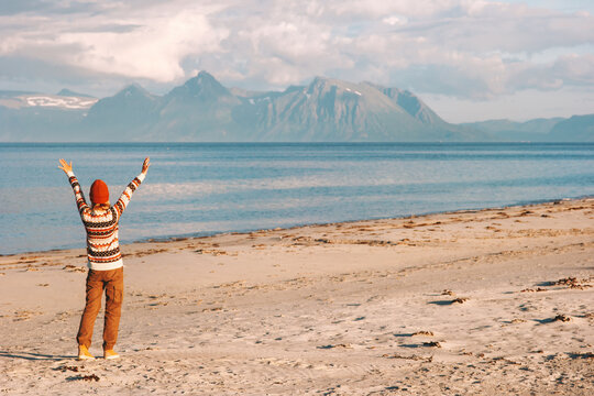 Woman traveler raised hands walking on sandy beach travel in Norway active healthy lifestyle trip vacations  outdoor enjoy life mental health concept