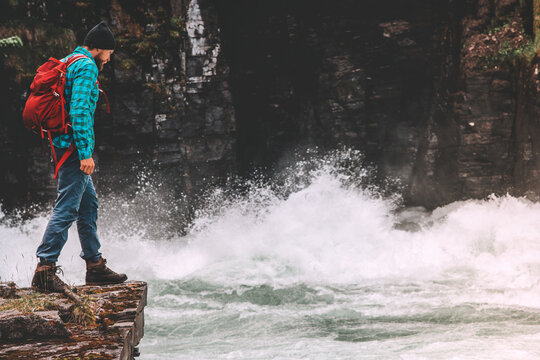 Adventurer man traveling in Sweden active hiking lifestyle backpacking solo hiker standing on cliff above river canyon vacation trip in wilderness