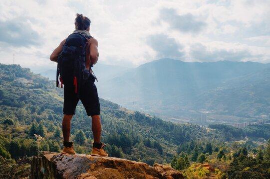 Young man standing with long hair without shirt and big backpack on rock in the mountain looking the city