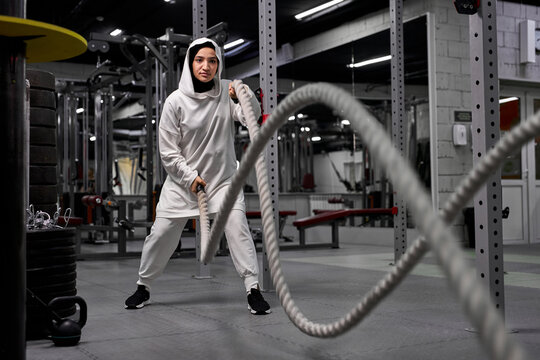 muslim athletic woman working out with ropes at cross fit gym copyspace confidence motivation sports lifestyle activity hobby healthy powerful femininity training concept