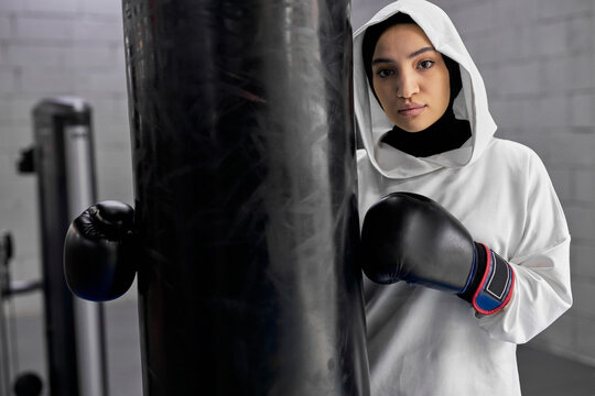fit arabic woman taking a break after hard boxing training, muslim female stands near punching bag posing at camera, in gym. woman in hijab