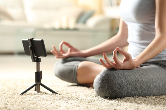 Female doing yoga watching online tutorial on mobile phone