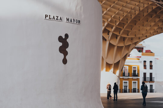 Seville, Spain - January 19, 2020: Plaza Mayor signs at the base of Metropol Parasol, Seville, Spain. Selective focus, people walk on background.