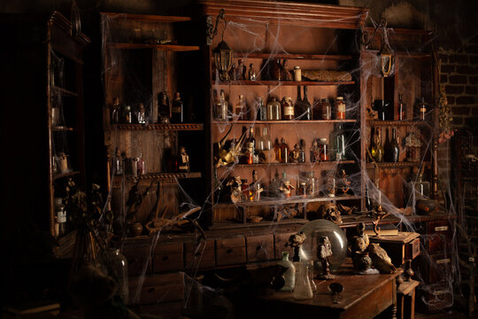 Halloween background Shelves with alchemy tools Skull spiderweb bottle with poison candles