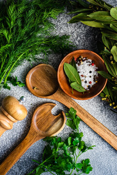 Rock salt, peppercorns, bay leaves, dill and parsley with salad serving spoons