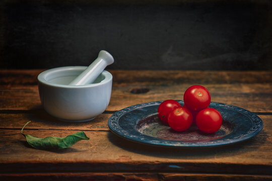 Cherry tomatoes on a plate next to a mortar and pestle on a wooden table