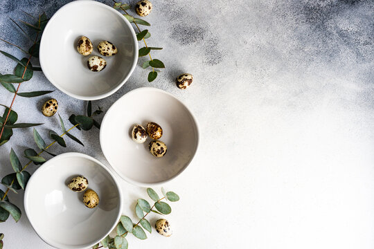 Easter table setting with bowls of Easter eggs and eucalyptus stems